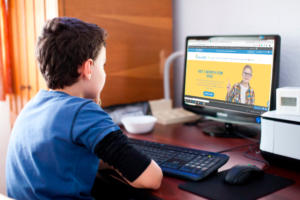 boy at computer with Ideal School on the computer monitor