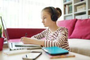 una niña que asiste a una escuela virtual en línea y escribe en un cuaderno
