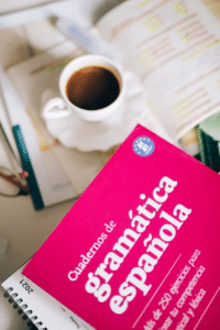 A Spanish grammar textbook next to a cup of coffee