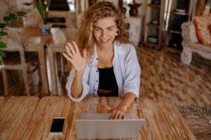 A teacher greeting her students in an online class