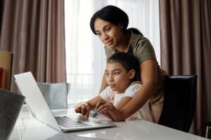 A mother helps her daughter with learning from home